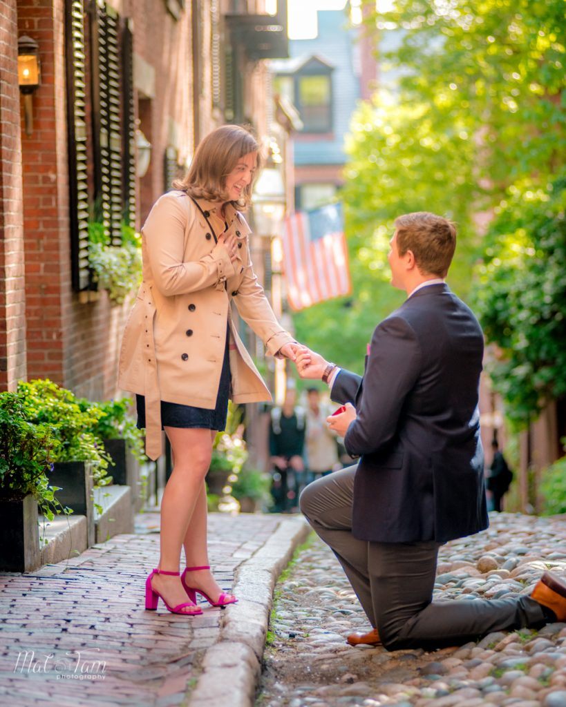 He's proposing to her at acorn street, with a large crowd watching
