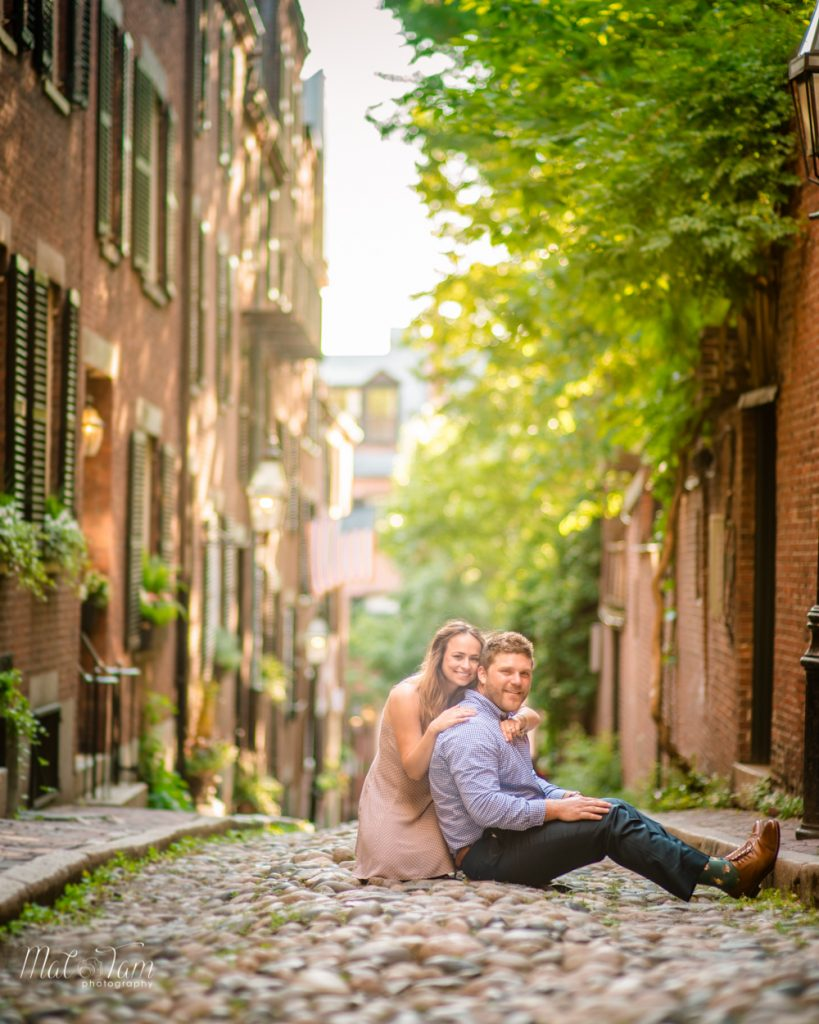 couple sitting on the cobblestone ground at acorn street