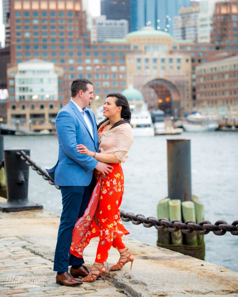 Newly engaged couple sharing a moment by the seaport front